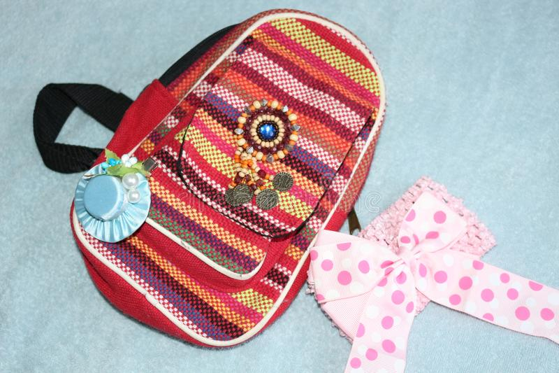 Red backpack for girls in ethno. Hair accessories are located near royalty free stock photography