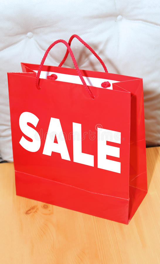 Red bag sale. Red shopping bag with sale sign on wooden floor stock images