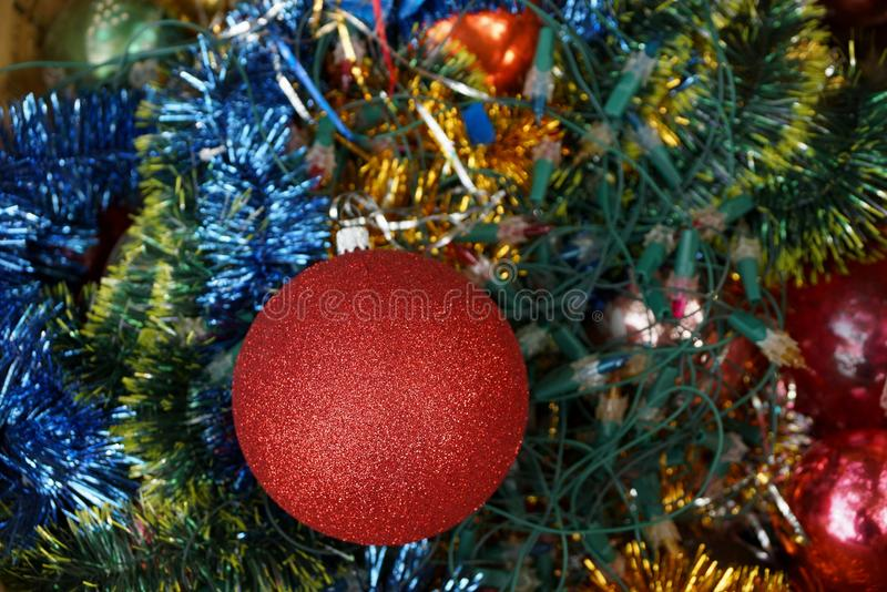 New Year`s ball in bright decorations and green needles. Red ball and bright colored Christmas decorations stock photos