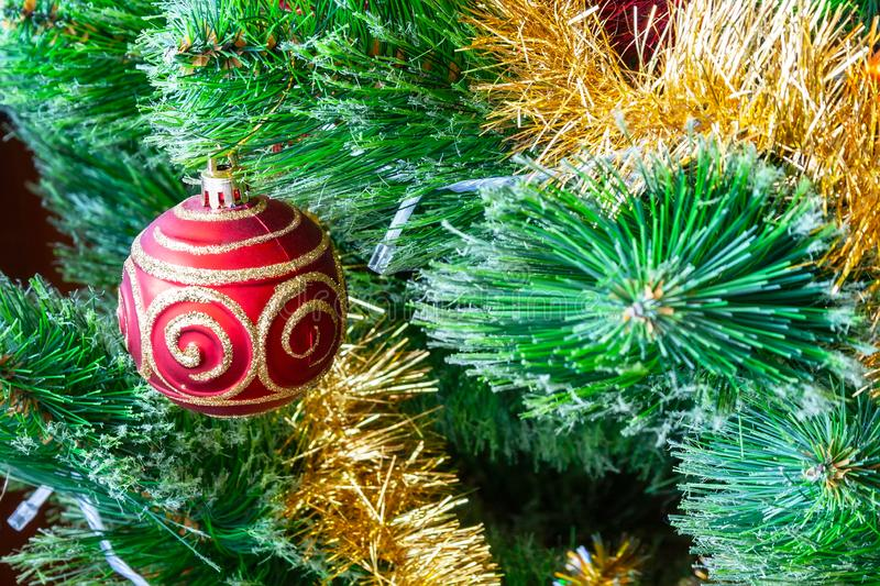 Red ball with gold glitter patterns hangs on a green artificial Christmas tree among the golden garlands for a family holiday stock photography