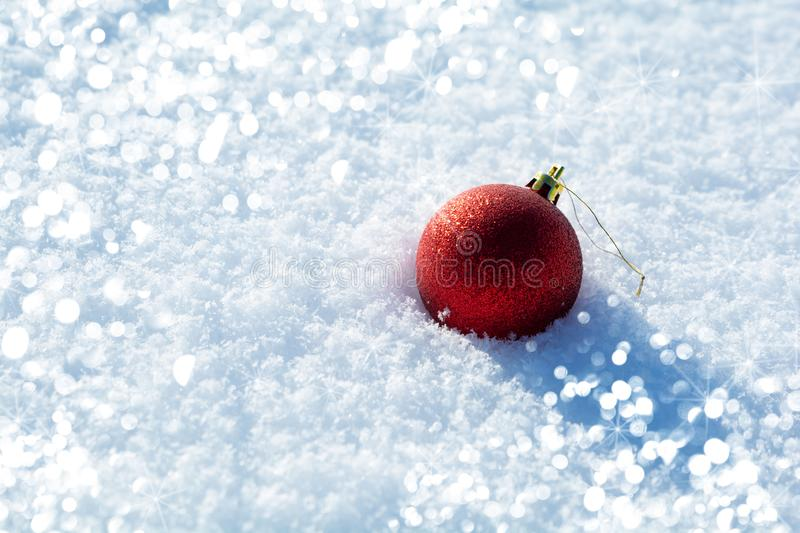 Red ball toy with lights on snow background. Christmas and New Year holidays celebration concept.  stock photos