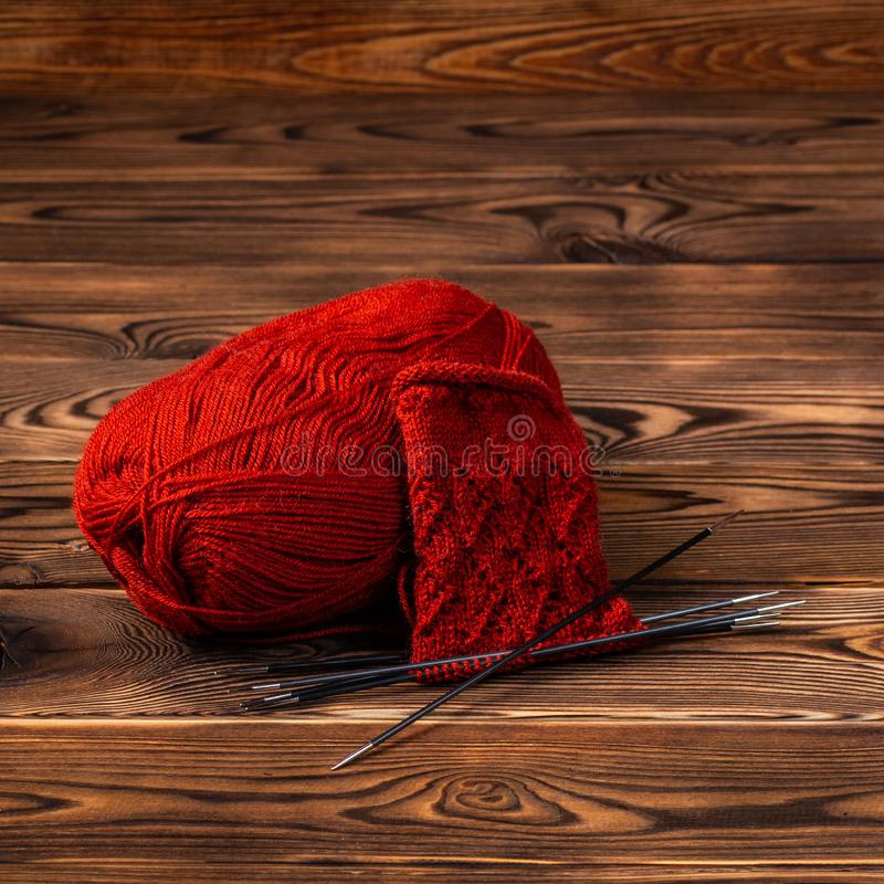 Red ball of yarn and knitting needles with knitting on wooden background royalty free stock images