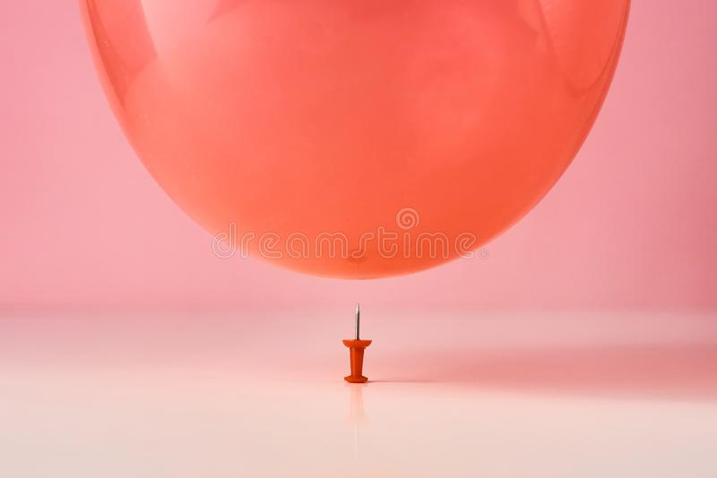Red balloon fall on a pin needle on pink background. Danger or protection concept. Red balloon fall on pin needle on pink background. Danger or protection royalty free stock photos