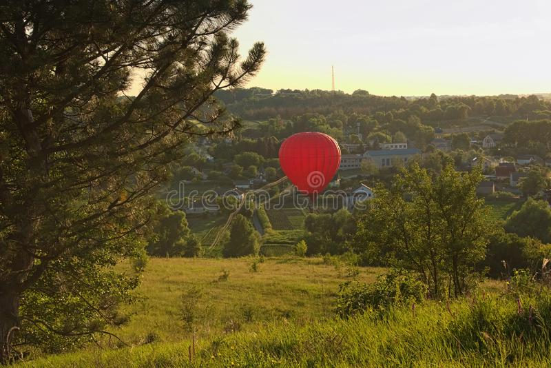 Red balloon flies over a village located between picturesque hills. Clear blue sky without clouds, during sunset royalty free stock images