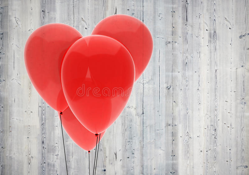 Red balloon heart on wood background. Red heart made of four balloons on light wood background stock photos