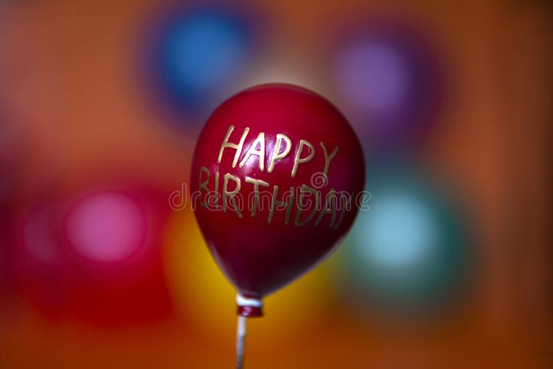 Red balloon with the inscription happy birthday flies up. On a festive color background royalty free stock photo