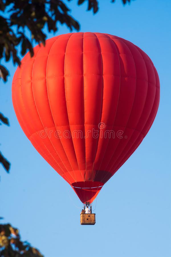 Red balloon in the sky. Aerostat. People in the basket. Fun. Summer entertainment. Romantic adventures.  royalty free stock photography