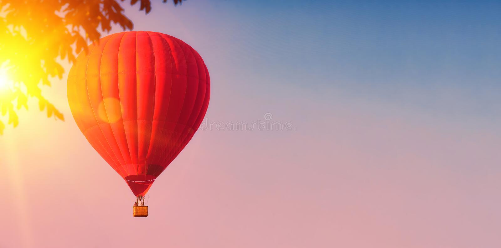 Red balloon in the sky. Aerostat. People in the basket. Fun. Summer entertainment. Romantic adventures. Modern toned photo. Retro. Colors stock photos