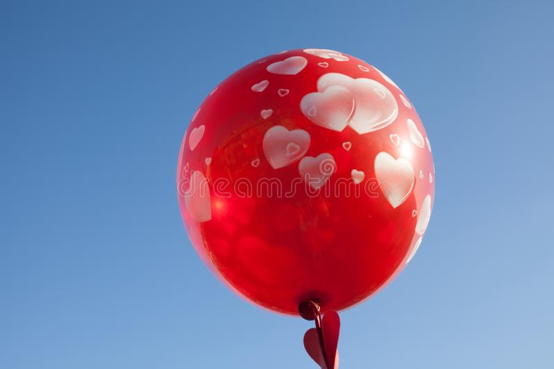 A little girl with red balloon on the blue sky. stock image
