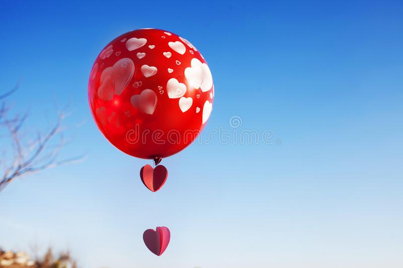 A little girl with red balloon on the blue sky. royalty free stock image