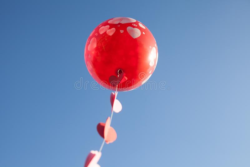 A little girl with red balloon on the blue sky. stock photo