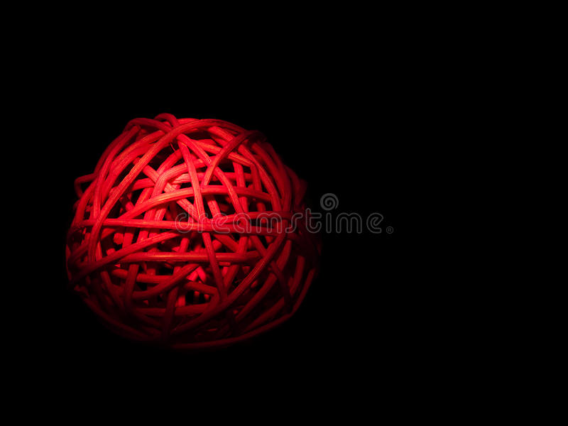 Red bamboo orb, illuminated over black. Seems to glow. Complicated interconnectedness concept royalty free stock images