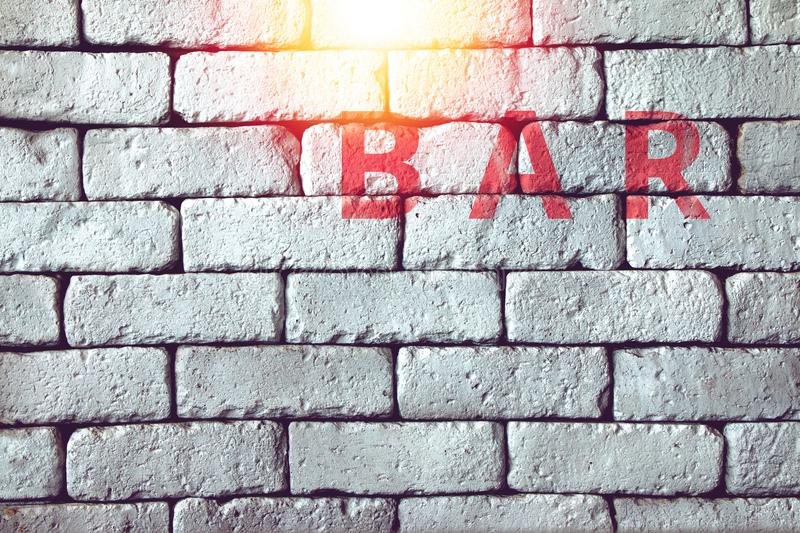 Red bar sign on white brick wall of underground pub royalty free stock photos