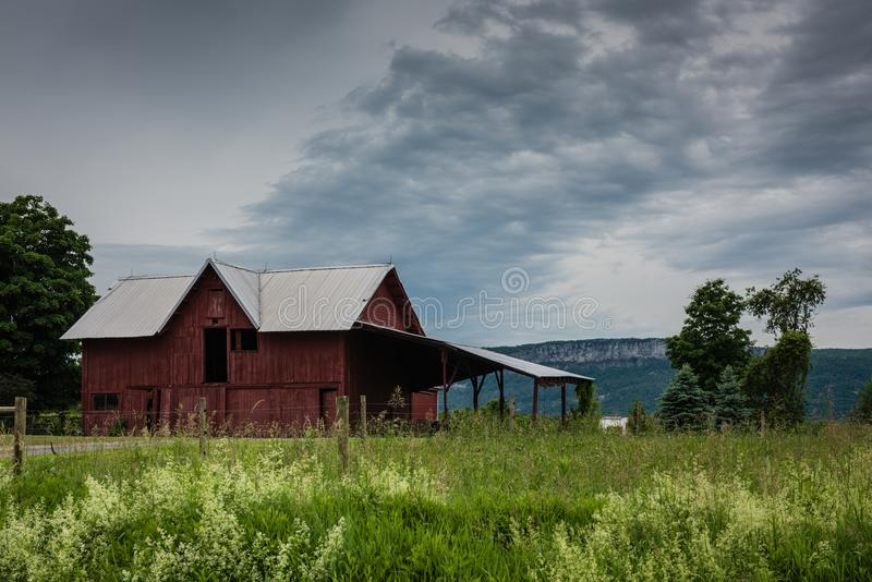Red Barn In Front of Shawangunk Mountains. Pine Bush, NY /USA - June 9, 2018: Red barn and grass field under a stormy sky with Shawangunk Mountains in background royalty free stock photos