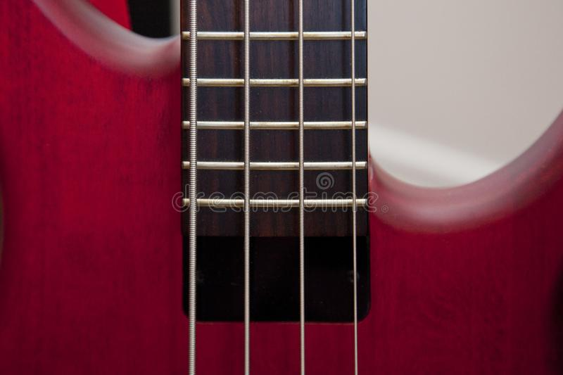 Red bass and fretboard. Bass guitar strings and frets on a beautiful red instrument royalty free stock photography