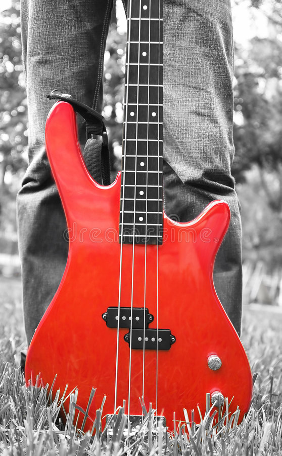 Red bass guitar on the grass. In black-and-white stock images
