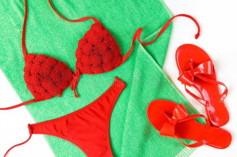Red bathing suit and red flip-flops on green towel. Summer cloth. Es stock images
