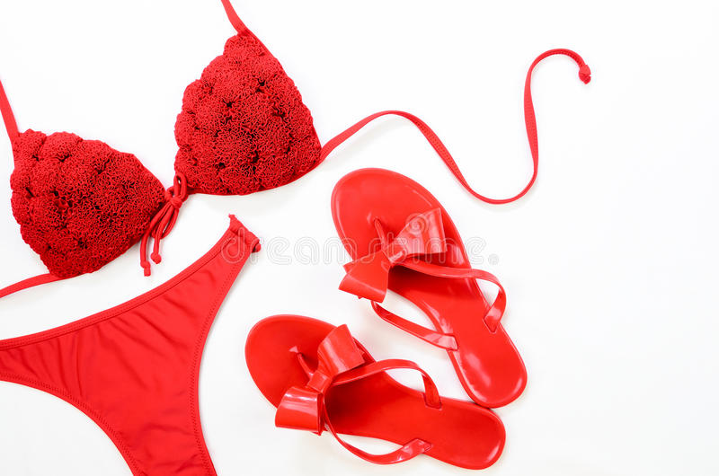 Red bathing suit and red flip-flops on white background. Summer. Clothes royalty free stock image