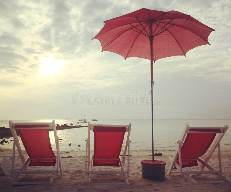Red beach beds and umbrella on the white beach sunset. Red beach beds and umbrella on white beach sunset royalty free stock image