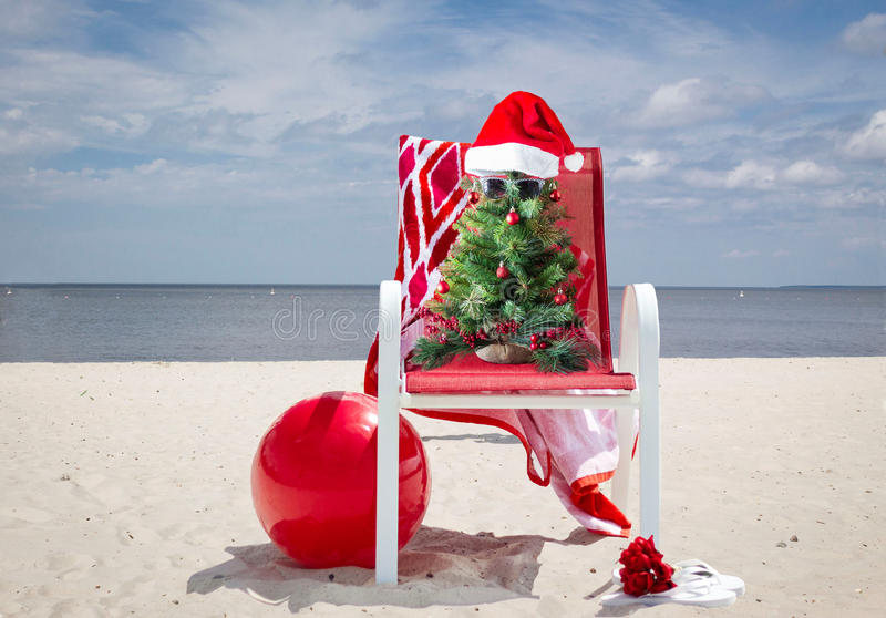 Red beach chair with a Christmas tree sitting in it at the beach. royalty free stock photography