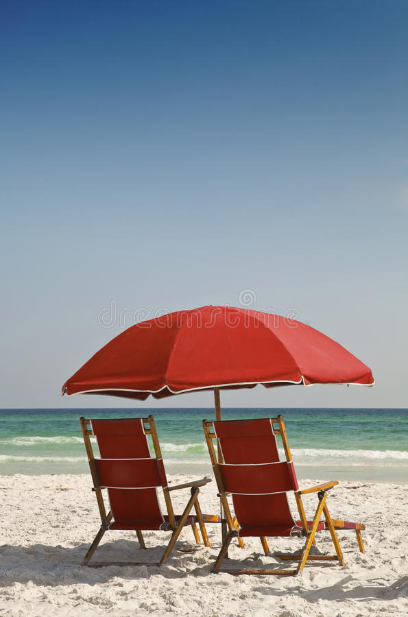 Red Beach Chairs and Umbrella. Two red canvas lounge chairs and red umbrella on a beautiful beach facing the ocean stock photography
