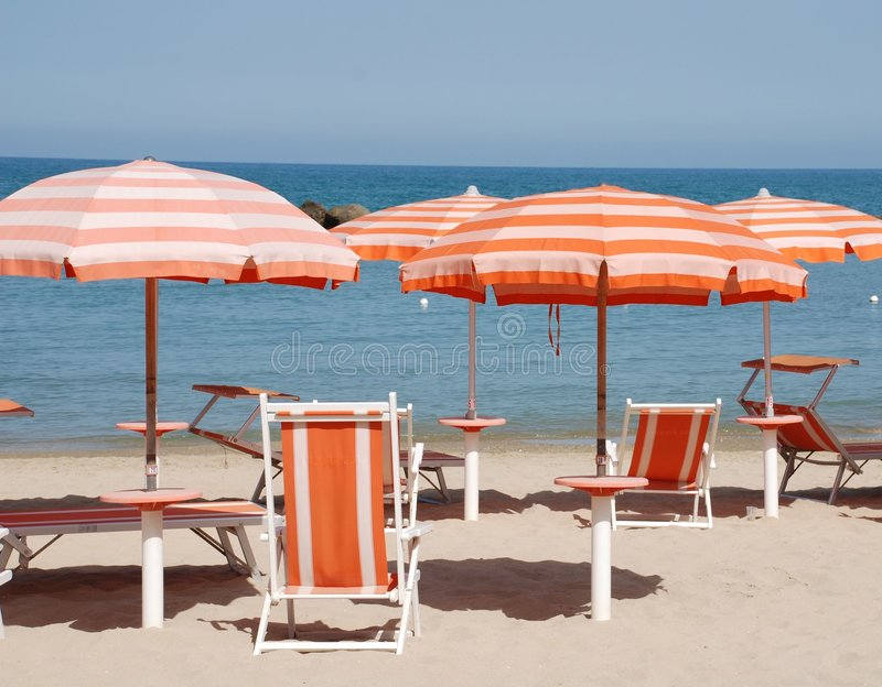 Red Beach Umbrellas. Red stripy beach umbrellas and deck chairs on a beach on a sunny summers day royalty free stock photos