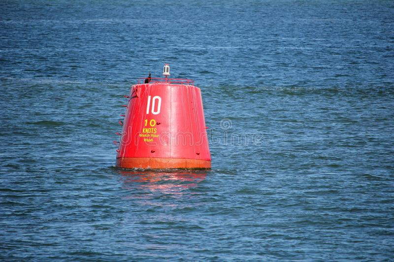 Red beacon buoy with speed limit of ten knots. Floating in blue sea or ocean stock photos