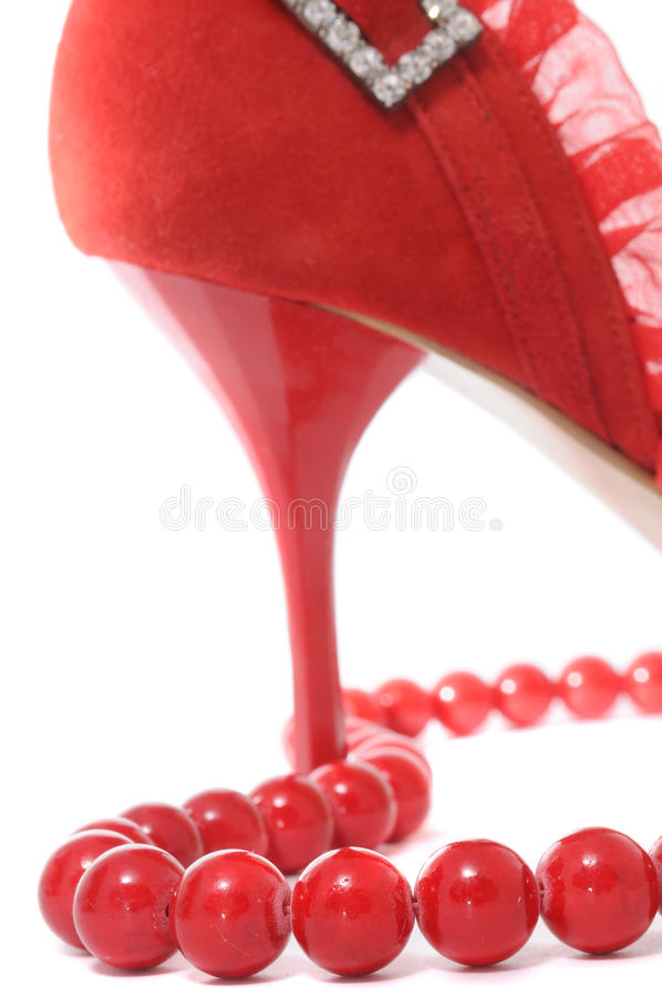 Red Beads and Stiletto Women's Shoe. Red beads and a red suede stiletto women's shoe royalty free stock images