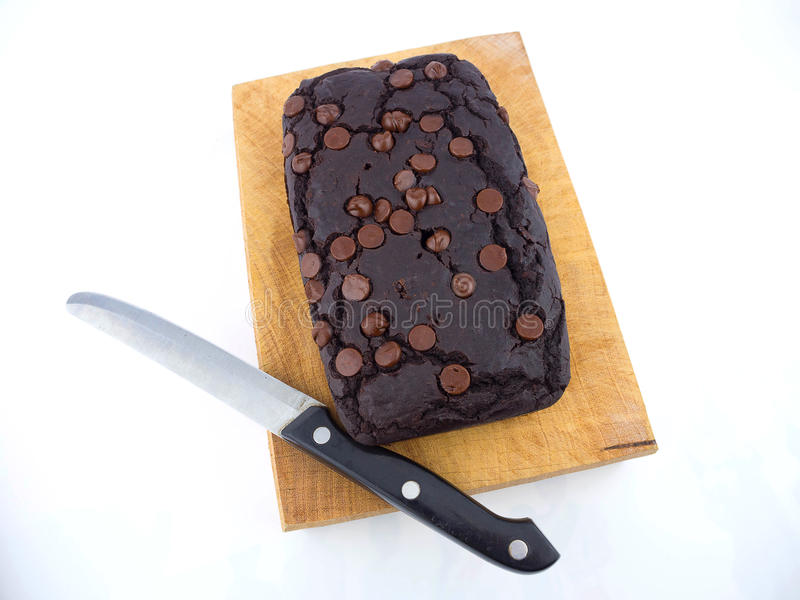 Red bean brownie loaf with chocolate chips on wooden cutting board with knife stock photos