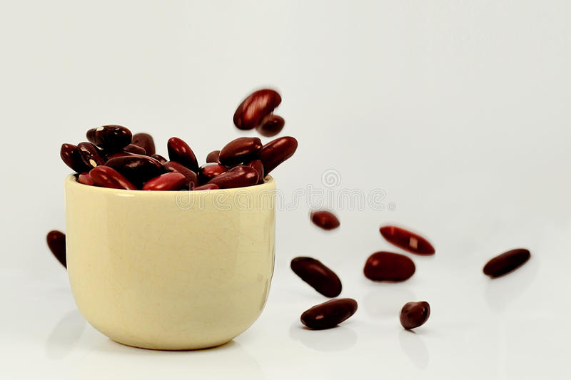 RED BEAN FALLING INTO THE CUP ON WHITE BACKGROUNG royalty free stock image