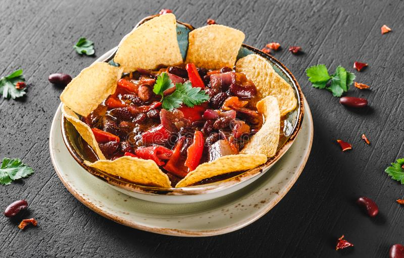 Red bean with nachos or pita chips, pepper and greens on plate over dark background. Mexican snack, Vegetarian food stock image