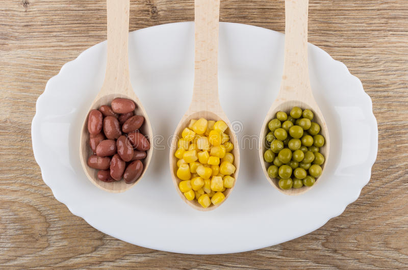 Red beans, green peas, sweet corn in spoons in dish. Red beans, green peas, sweet corn in wooden spoons in dish on wooden table. Top view stock photo