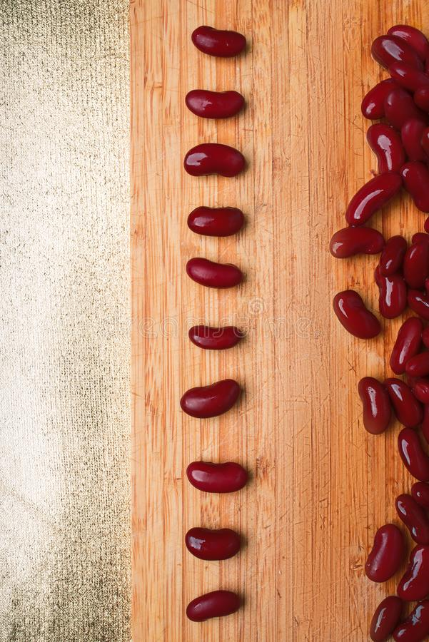 Red beans are laid out on a wooden background, vertical frame royalty free stock images