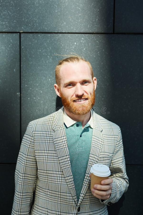 Red-bearded businessman with takeout drink. Portrait of smiling red-bearded businessman in stylish checkered jacket drinking coffee from takeout cup royalty free stock images