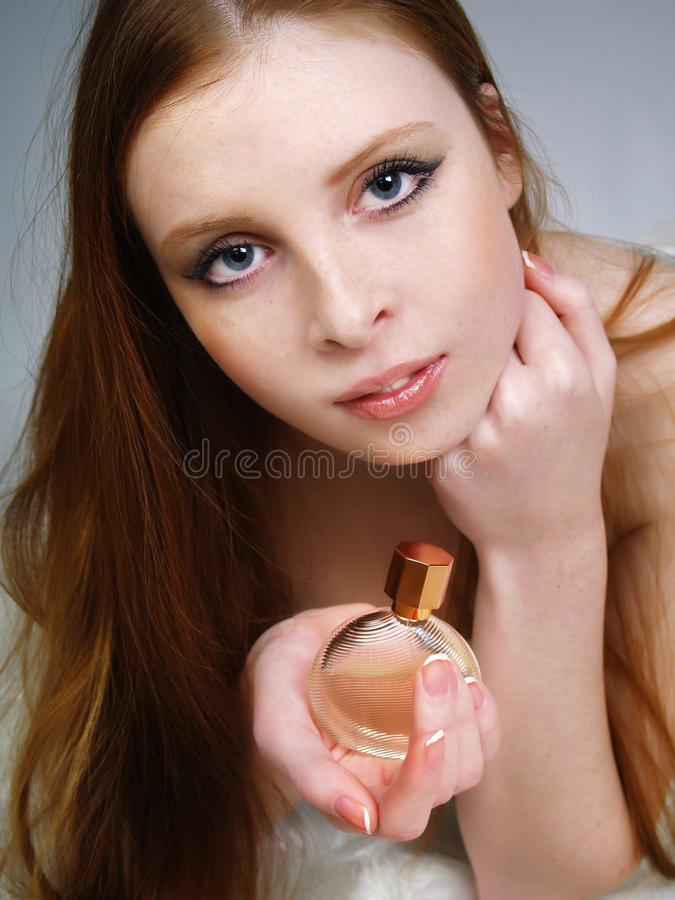 The red beautiful girl holds a bottle with spirits stock image