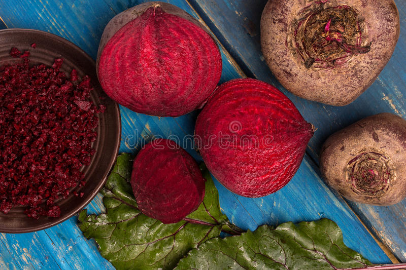 Red beet. Composition with red beet on a blue wooden table royalty free stock photography