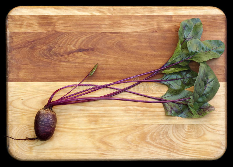 Red Beet on Cutting Board. Fresh red beet (Detroit Dark Red variety) with leaves on wooden cutting board on black background stock image