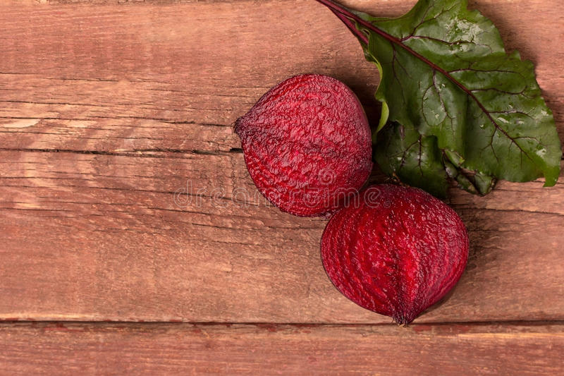 Red beet. Two half of red beet on a wooden table royalty free stock photo