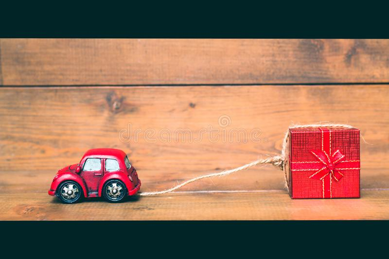 Red beetle car are dragging red gift box on old and vintage. Rustic wooden background. using for Christmas greeting card, New Year and happy birthday present stock photography
