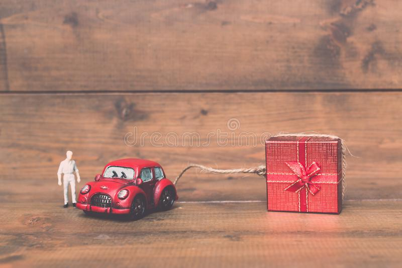 Red beetle car are dragging red gift box on old and vintage. Rustic wooden background. using for Christmas greeting card, New Year and happy birthday present royalty free stock photography
