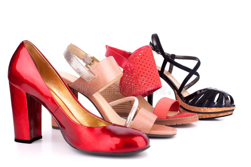 Red, beige, orange and black female shoes and sandals with high heels for sale side view on white background  close up. Red, beige, orange and black female shoes royalty free stock photography