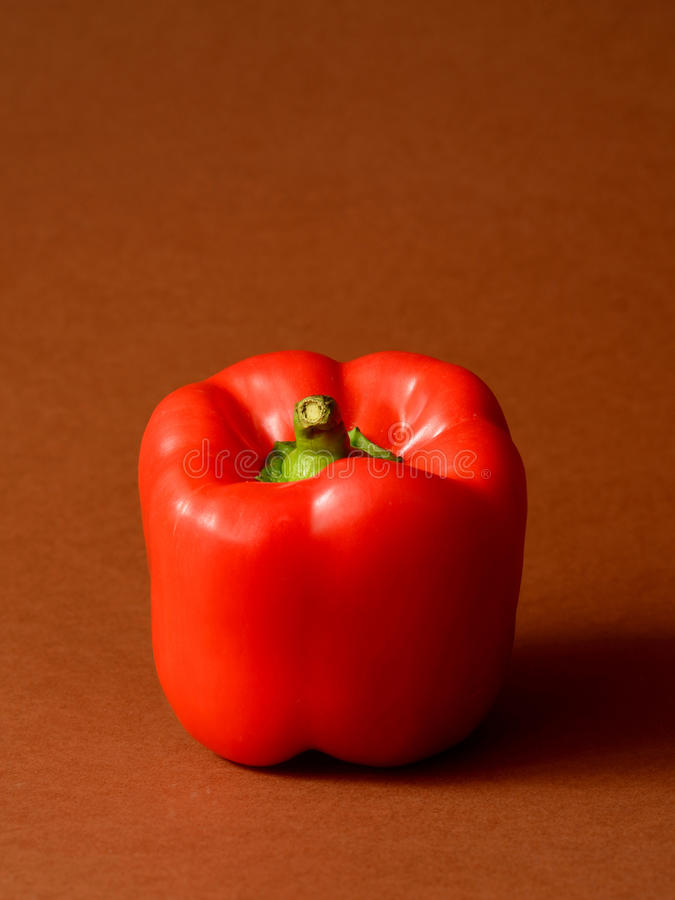 Red Bell pepper. On a brown background royalty free stock photography