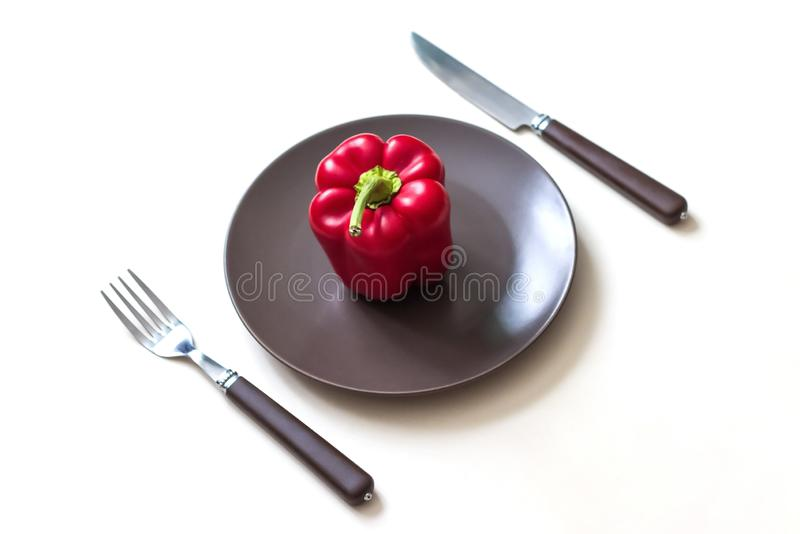 Red bell pepper on a brown plate and cutlery. Isolated white background royalty free stock images