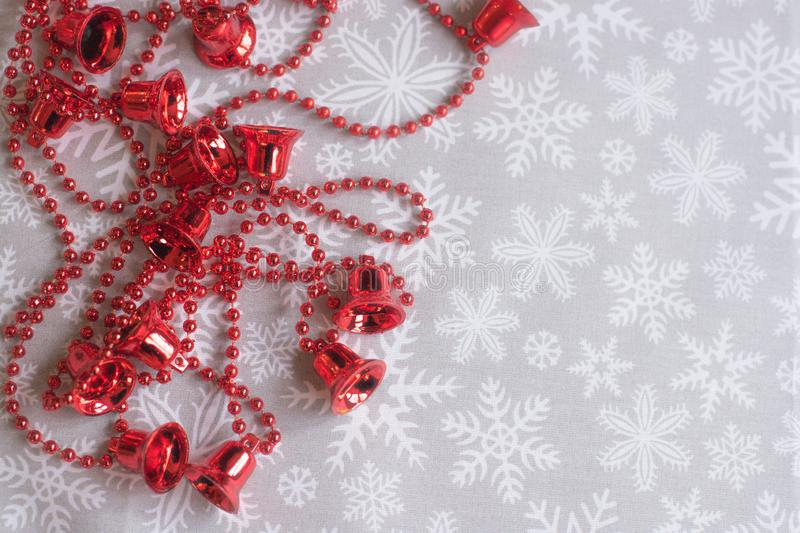 Red bells on the snowflake background. Space for. text stock images