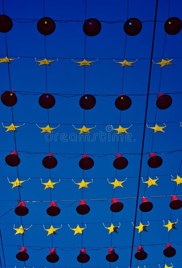 Red bells and yellow stars hanging on rope. Bottom view of red bells and yellow stars hanging on rope with blue sky background stock image