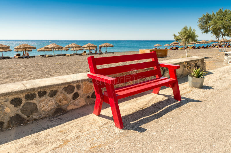Red bench along the beach stock photography