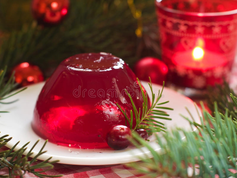 Red berries jelly. A red berries jelly on a plate with christmas tree in the background, selective focus stock image