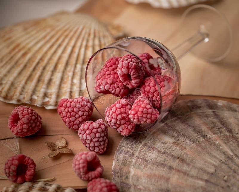 red berries raspberries braun background glass shells royalty free stock photos