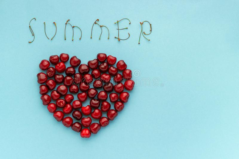 Red berry cherries in shape of heart and text SUMMER, Still life on blue background. Flat lay, Top view. Copy space Concept. Love of cherry and summer stock image