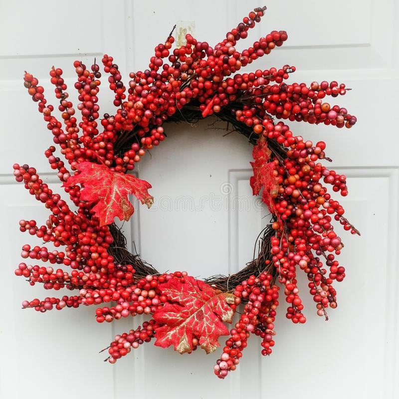 Red Berry Fall Leaf Wreath Hanging on White Door. A red berry, fall leaf wreath hanging on a white door stock photography